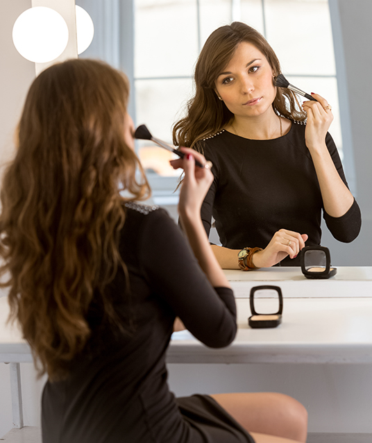 young elegant woman doing makeup at mirror with bulbs